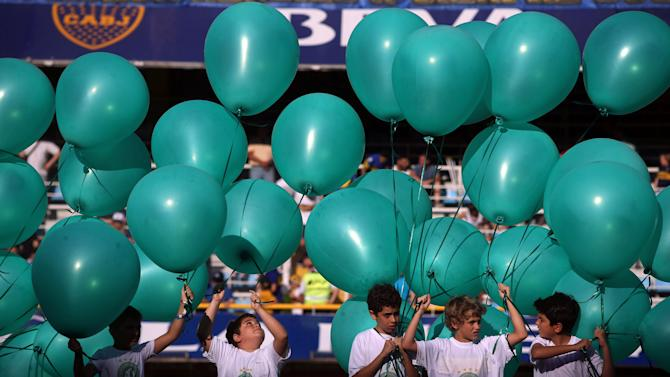 Children hold green balloons to pay tribute to the victims of the plane crash in Colombia in Buenos Aires