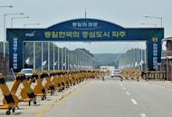 Cars drive past barricades on the road linking North Korea's Kaesong Industrial Complex at a military check point in Paju near the demilitarized zone dividing the two Koreas on June 6, 2013. North Korea on Wednesday restored its hotline with South Korea and announced it would let the South's businessmen visit a shuttered joint industrial zone, Seoul officials said