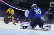 Sweden's Loui Eriksson (L) scores on Slovenia's goalie Robert Kristan during the third period of their men's quarter-finals ice hockey game at the Sochi 2014 Winter Olympic Games February 19, 2014. REUTERS/Martin Rose/Pool