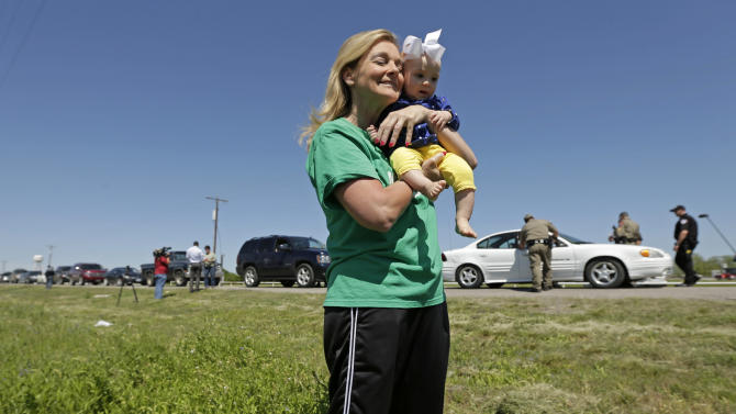 Displaced resident Debby Keel holds her granddaughter Kennedy Keel as she waits by a checkpoint for residents waiting to go back to their homes Saturday, April 20, 2013, three days after an explosion at a fertilizer plant in West, Texas. The massive explosion at the West Fertilizer Co. Wednesday night killed 14 people and injured more than 160. (AP Photo/Charlie Riedel)