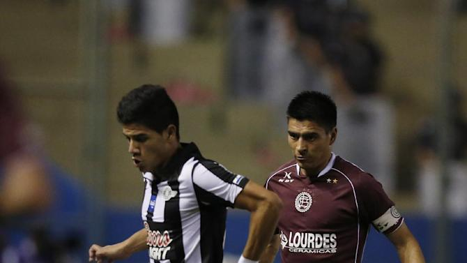 Jose Recalde of Paraguay's Libertad, left, fights for the ball with Paolo Goltz of Argentina's Lanus at a Copa Sudamericana soccer game in Asuncion, Paraguay, Thursday, Nov. 21, 2013