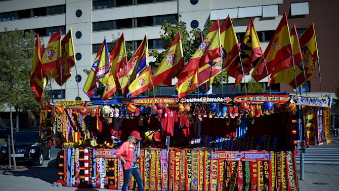 A woman walks in front of a kiosk selling football scarves and Spanish flags before Spain-Luxembourg Euro 2016 Group C qualification soccer match in Logrono