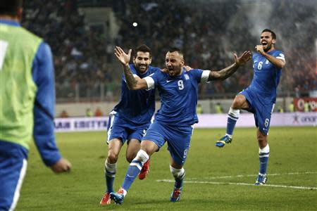 Greece's Mitroglou, Siovas and Tziolis celebrate a goal against Romania during their 2014 World Cup qualifying playoff first leg soccer match in Piraeus
