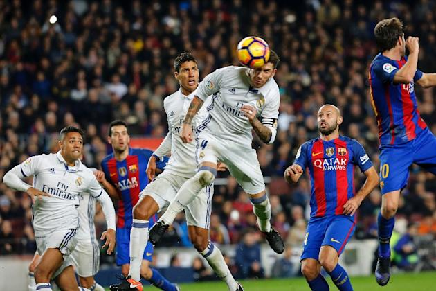Real Madrid's defender Sergio Ramos (C) heads a ball to score the equalizer past Real Madrid's Raphael Varane (3rdL) and Barcelona's defender Javier Mascherano (R) during the Spanish leagu