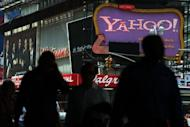 Pedestrians walk by a Yahoo! sign in Times Square in New York City. Yahoo! on Tuesday revealed that it will dump products in a quest to return the faded Internet star to glory