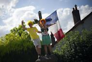 Fans wave a French flag as they wait for riders during the 41.5 km individual time-trial and ninth stage of the 2012 Tour de France cycling race starting in Arc-et-Senans and finishing in Besancon, eastern France