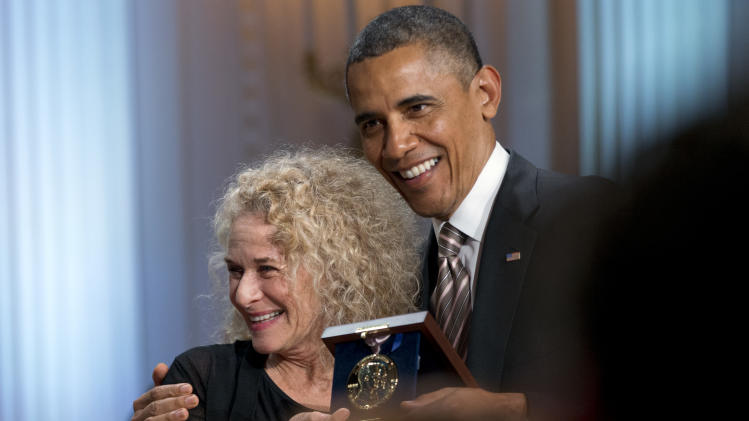 President Barack Obama presents the Library of Congress Gershwin Prize for Popular Song during an East Room concert honoring singer-songwriter Carole King, Wednesday, May 22, 2013, at the White House in Washington. King is the first woman to receive the award. (AP Photo/Jacquelyn Martin)