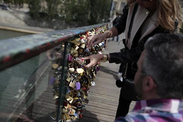 """A couple locks a padlock on the """"Pont des Arts"""" on May 29, 2015, in Paris"""