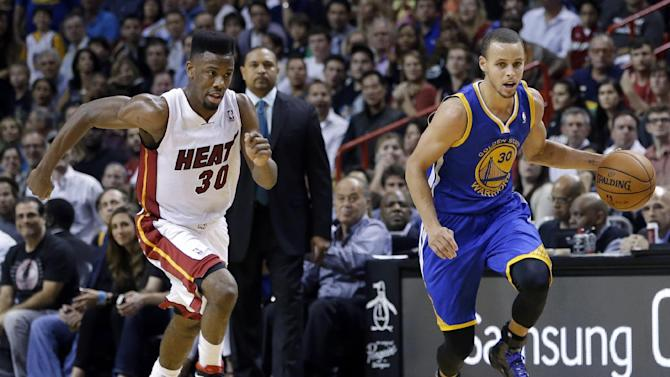Golden State Warriors' David Lee (10) brings the ball up as Miami Heat's Norris Cole (30) follows during the second half of an NBA basketball game, Thursday, Jan. 2, 2014, in Miami. The Warriors defeated the Heat 123-114