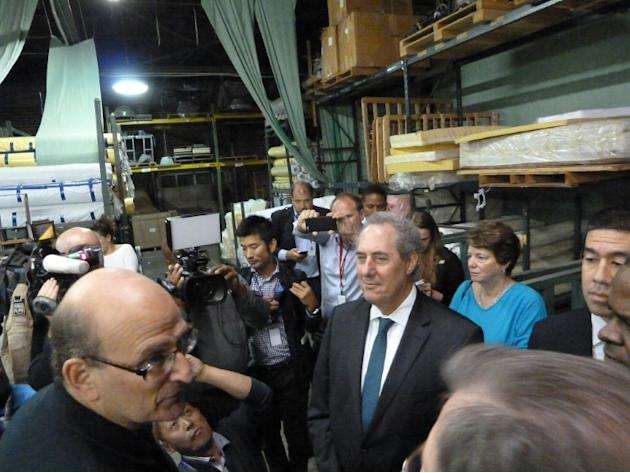 US Trade Representative Michael Froman(C) takes a break from negotiations on the Trans-Pacific Partnership trade treaty in Atlanta, Georgia to visit the Colgate mattress factory on October 1, 2015