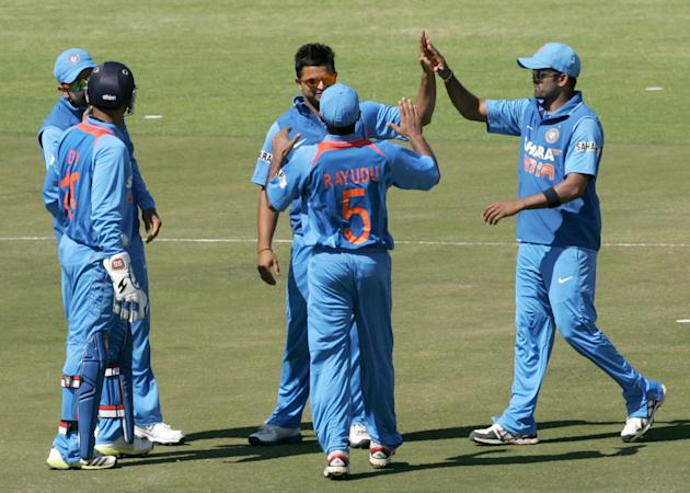India's Suresh Raina (C) is congratulated by teammates after getting a wicket during the first of the five ODI cricket series matches between India and hosts Zimbabwe at the Harare Sports Club on