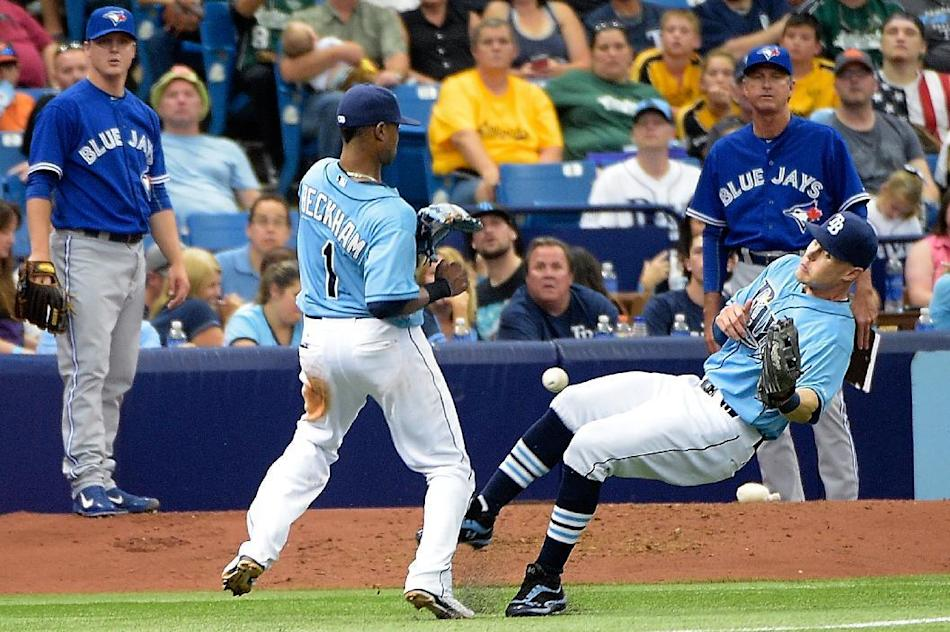 Tampa Bay Rays left fielder Brandon Guyer, right, drops a pop fly hit foul by Toronto Blue Jays' Dalton Pompey as shortstop Tim Beckham (1) watches during the eighth inning of a baseball game in S