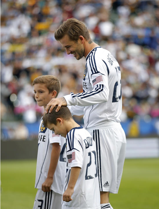 Los Angeles Galaxy's David Beckham, of England, walks with his sons, Romeo, background, left, and Cruz before the MLS Cup championship soccer match against the Houston Dynamo in Carson, Calif., Saturd
