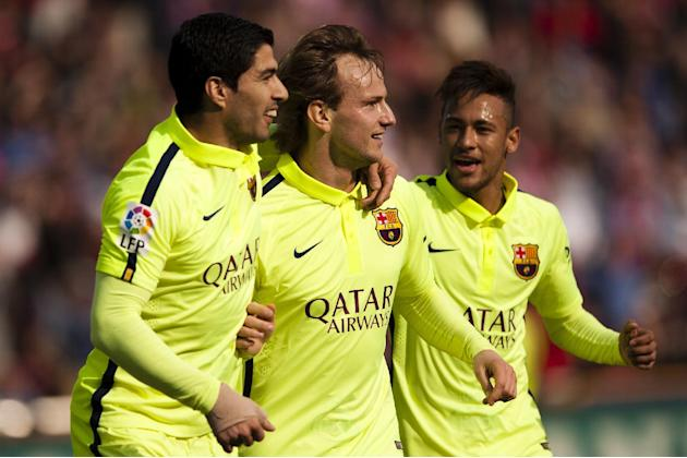 Barcelona's Ivan Rakitic, center, celebrates his goal with teammates Luis Suarez, left, and Neymar during a Spanish La Liga soccer match between Granada and FC Barcelona at Los Carmenes stadium in