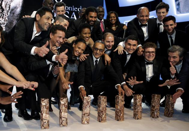 Director Abderrahmane Sissako poses with team members and the trophies received for the film