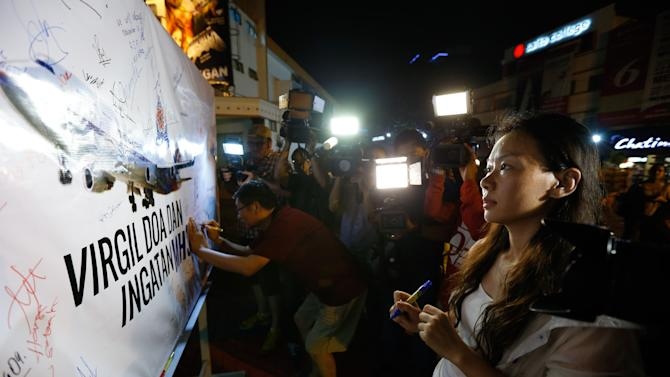 Kelly Wen, wife of Chinese passenger onboard the missing Malaysia Airlines Flight MH370 looks at a MAS airplane poster during an event to mark one year anniversary of the pane disappearance, during a candlelight vigil for passengers onboard the missing Malaysia Airlines Flight MH370 in Kuala Lumpur, Malaysia, on Friday, March 6, 2015. (AP Photo/Vincent Thian)