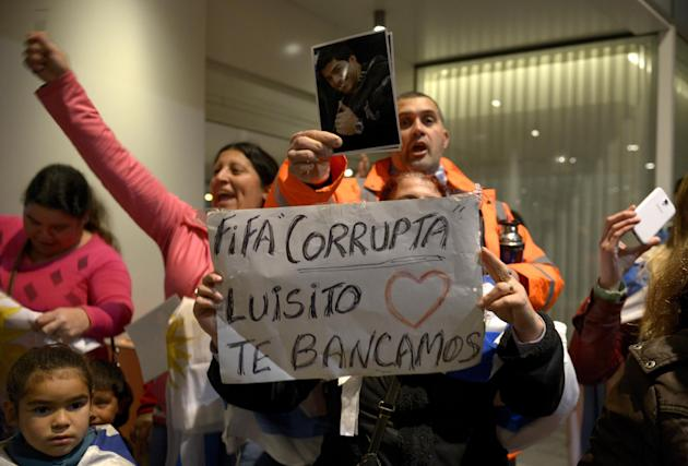 "Fans of Uruguay's national soccer team await the arrival of Uruguay's player Luis Suarez with a sign that reads in Spanish ""FIFA Corrupt, Luis, we support you"", at Carrasco International Airport in the outskirts of Montevideo, Uruguay, Thursday, June 26, 2014. The Uruguay forward, widely regarded as one of the best players in the world, was banned by FIFA from all football for four months on Thursday for biting an Italian opponent in an incident that marred the team's victory and progression to the second round. (AP Photo/Matilde Campodonico)"