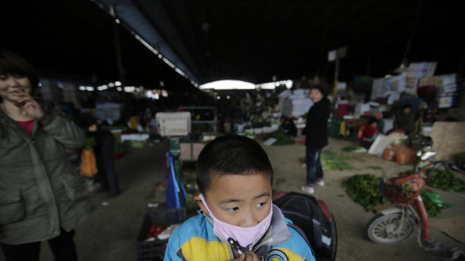 In this April 9, 2013 photo, a child wears a mask near the closed poultry section at the Huhuai agricultural market where the H7N9 bird flu was detected by authority in Shanghai, China. After a new and lethal strain of bird flu emerged in Shanghai two weeks ago, the government of China's bustling financial capital responded with live updates on a Twitter-like microblog. It's a starkly different approach than a decade ago, when Chinese officials silenced reporting as a deadly pneumonia later known as SARS killed dozens in the south. (AP Photo/Eugene Hoshiko)