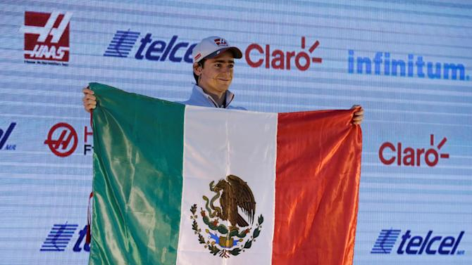 Haas Formula One driver Gutierrez of Mexico holds up Mexico's flag after attending a news conference at the Plaza Carso in Mexico City
