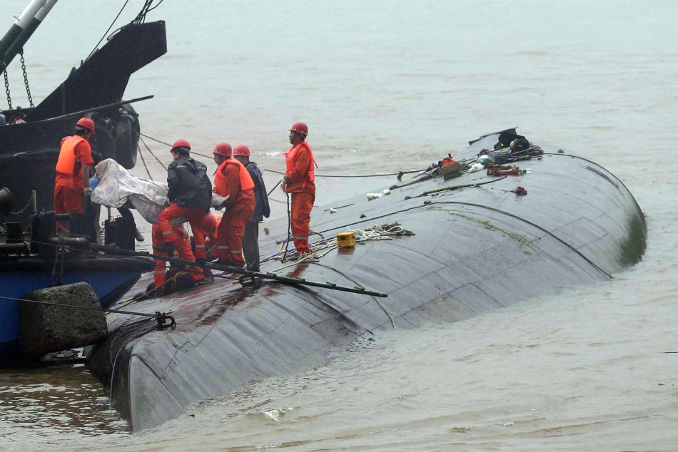 Rescue workers remove a body from the hull of a capsized ship on the Yangtze River in Jianli in central China's Hubei province, Tuesday, June 2, 2015. Divers on Tuesday pulled three people alive from