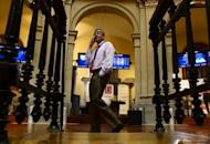 A trader speaks on his mobile phone next to the IBEX-35 index billboard at Madrid's stock exchange. World markets cast Spain back to the centre of the eurozone debt storm Monday, pushing its borrowing rate to a euro-era record and dashing hopes for a respite after Greek elections