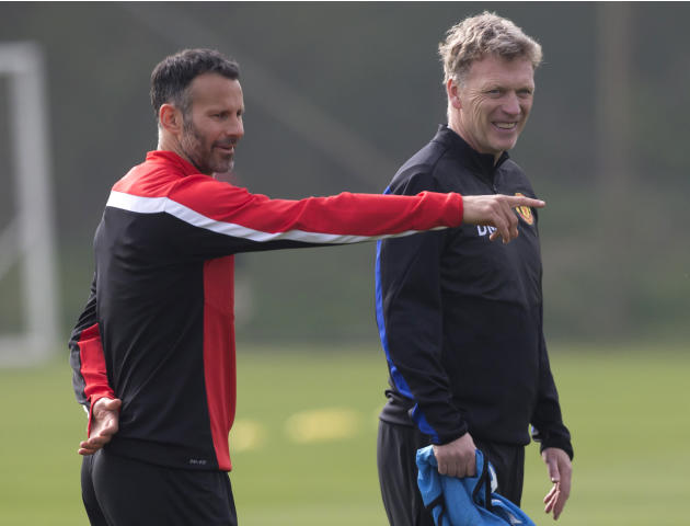 FILE - In this Monday, March 31, 2014 file photo Manchester United's manager David Moyes, right, stands alongside Ryan Giggs as the team trains at Carrington training ground in Manchester. Manches