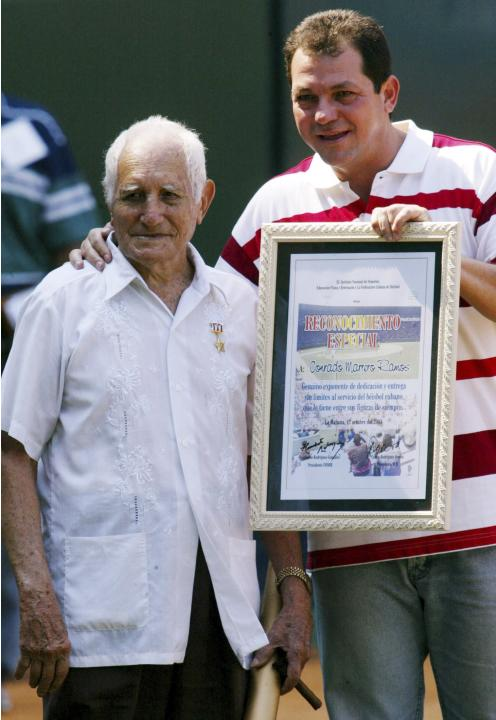 File photo of veteran baseball player Conrado Marrero standing next to Humberto Rodriguez, president of the Cuban Sports Federation in Havana