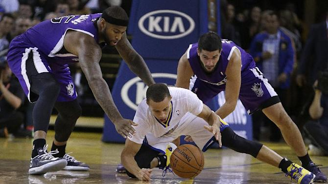 Sacramento Kings' DeMarcus Cousins, left, and Greivis Vasquez, right, chase a loose ball with Golden State Warriors' Stephen Curry during the second half of an NBA basketball game on Saturday, Nov. 2, 2013, in Oakland, Calif
