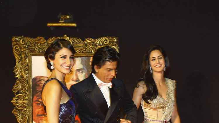 "In this Monday, Nov. 12, 2012 photo, Bollywood stars Anushka Sharma, left, Shah Rukh Khan, center, and Katrina Kaif walk during the premier of their film ""Jab Tak Hai Jaan"" or ""As long as I Am Alive"" in Mumbai, India. Bollywood stars turned out in strength at the premiere of the movie for a final homage to movie mogul Yash Chopra, who died last month days after finishing the film. Chopra was known as the ""King of Romance"" for creating classic love stories that were immensely popular. (AP Photo/Rafiq Maqbool)"