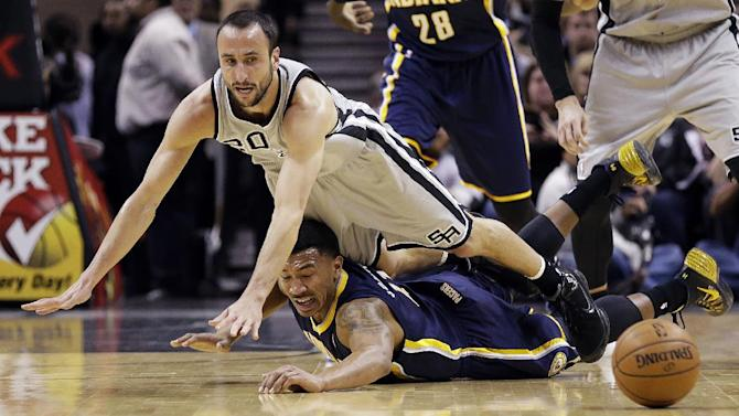 San Antonio Spurs' Manu Ginobili (20), of Argentina, and Indiana Pacers' Orlando Johnson, bottom, dive for a loose ball during the first half on an NBA basketball game Saturday, Dec. 7, 2013, in San Antonio