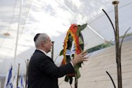 Israeli Prime Minister Benjamin Netanyahu lays a wreath on Remembrance Day, April 24. Netanyahu said that Iran should remain under biting sanctions until it halts all uranium enrichment, appearing to exceed UN demands on Tehran