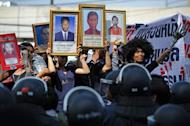 """Protesters hold up pictures of some of those killed during a crackdown on anti-government rallies two years ago as former Thai prime minister Abhisit Vejjajiva (not pictured) appears at a justice ministry building to be charged with murder over a civilians' death, in Bangkok on December 13, 2012. Terrorism trial against Thai leaders of the 2010 """"Red Shirt"""" protests began on Friday"""
