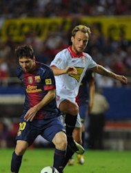 Barcelona's Lionel Messi (L) fights for the ball with Sevilla's Ivan Rakitic during their Spanish La Liga match at the Ramon Sanchez Pizjuan stadium in Sevilla. Barcelona won 3-2