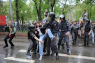 Police officers escort an anti-Putin protester who was detained in central Moscow, on May 7, 2012. Thousands of Muscovites were due to rally Sunday in commemoration of a bloody protest one year ago in which more than 400 were detained after showing their frustration with Vladimir Putin's return to the presidency