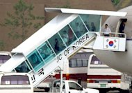This file photo shows a group of North Korean refugees getting off a plane upon arrival at Seongnam military airport, south of Seoul, in 2004. North Koreans often travel on from China to Southeast Asian countries such as Thailand, Vietnam and Laos in hopes of flying from there to South Korea