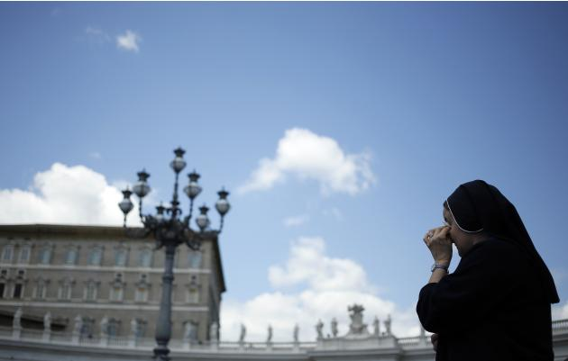 A nun wipes her eye as she stands in St.Peter's square at the Vatican