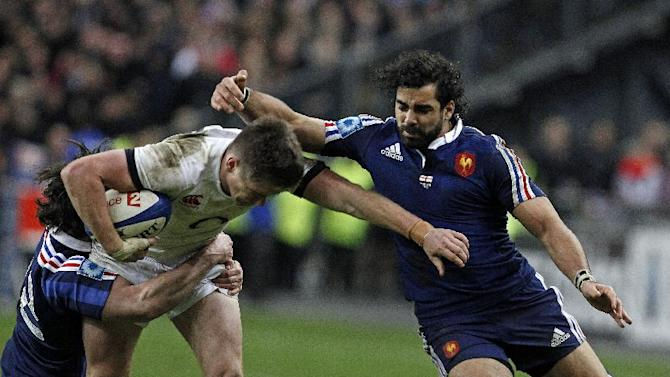 England's Owen Farrell is tackled by France's Yoann Huget, right, and Maxime Machenaud, during their Six Nations rugby union international match, at the Stade de France, in Saint Denis, outside Paris, Saturday, Feb 1, 2014. France defeated England 26-24. (AP Photo/Thibault Camus)