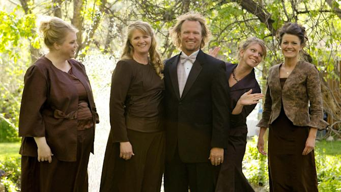 "FILE - In this undated file photo provided by TLC, Kody Brown, center, poses with his wives, from left, Janelle, Christine, Meri, and Robyn in a promotional photo for TLC's reality TV show, ""Sister Wives.""  A Utah county attorney says he will not pursue criminal charges against this polygamous family made famous by a reality TV show. A federal judge is set to decide whether to allow a lawsuit to move forward that challenges the constitutionality of Utah's bigamy law. (AP Photo/TLC, Bryant Livingston, File)"
