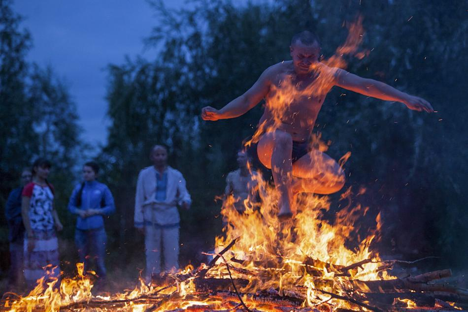 A man jumps over a campfire during a celebration of the traditional Ivana Kupala (Ivan the Bather) holiday near Omsk, Russia