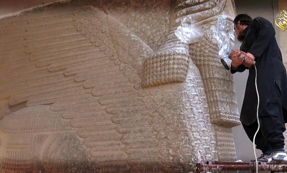 An image grab taken off a video reportedly released by Media Office of the Nineveh branch of the Islamic State (IS) Group on February 25, 2015, shows an IS militant destroying the statue of Lamassu, an Assyrian deity, with a jackhammer in the northern Iraqi Governorate of Nineveh. (AFP PHOTO)
