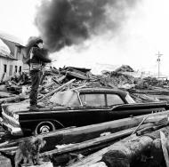 File - In this March 29, 1964 file photo, a photographer looks over wreckage as smoke rises in the background from burning oil storage tanks at Valdez, Alaska, March 29, 1964. The city was hit hard by the earthquake that demolished some of Alaska's most picturesque and largest cities. North America's largest earthquake rattled Alaska 50 years ago, killing 15 people and creating a tsunami that killed 124 more from Alaska to California. The magnitude 9.2 quake hit at 5:30 p.m. on Good Friday, turning soil beneath parts of Anchorage into jelly and collapsing buildings that were not engineered to withstand the force of colliding continental plates.(AP Photo/File)