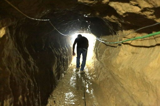 A Palestinian man walks from the Egyptian side of the border in a repaired bombed smuggling tunnel linking the Gaza Strip to Egypt, in Rafah, on November 29, 2012. Israel is to begin allowing materials for private construction into Gaza, easing its blockade under the terms of a truce deal, Israeli and Palestinian officials said on Wednesday
