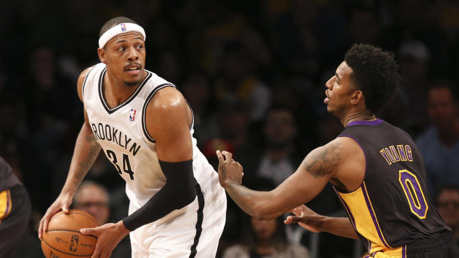 Brooklyn Nets small forward Paul Pierce (34) looks to pass around Los Angeles Lakers small forward Nick Young (0) in the second half of an NBA basketball game at the Barclays Center, Wednesday, Nov. 27, 2013, in New York. The Lakers defeated the Nets 99-94