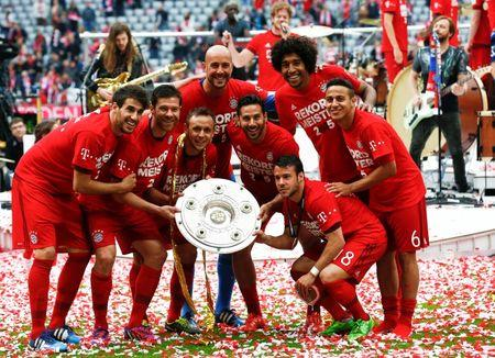Bayern Munich's players pose with the trophy after their final German first division Bundesliga soccer match of the season against FSV Mainz 05 in Munich