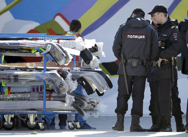 FILE - In this Feb. 10, 2014 file photo, police officers look over a cart of hockey sticks after they were taken off a plane as NHL hockey players arrive at the Sochi International Airport for the 201