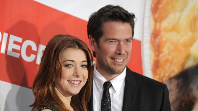 "FILE - This March 19, 2012 file photo shows actress Alyson Hannigan, a cast member in ""American Reunion,"" posing with her husband, actor Alexis Denisof, at the premiere of the film in Los Angeles. Hannigan obtained a temporary restraining order on Wednesday, Feb. 13, 2013 claiming a New Hampshire man recently released from a mental institution has been threatening to kill her and harm her family in online postings. (AP Photo/Chris Pizzello, file)"