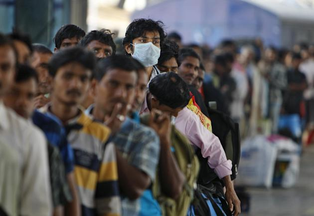 An Indian man wears a protective mask as he stands in a queue to board a train at the Secunderabad railway station in Hyderabad, India, Wednesday, Feb. 25, 2015.Health officials in India are strugglin