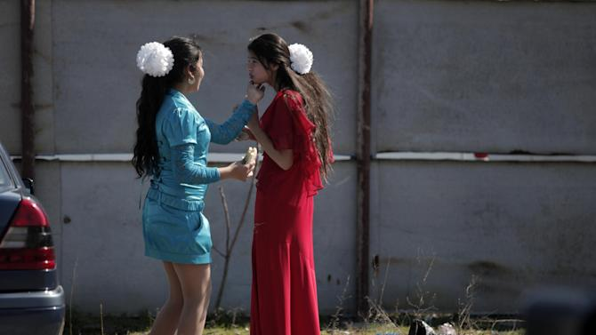 """This Saturday, March 23, 2013  photo shows Roma brides-to-be from the Kalaidzhi community preparing for  so called """"Roma bridal market"""". The Kalaidzhi, who represent only a small portion of the estimated 700,000 Roma in Bulgaria, are almost all devout Orthodox Christians who keep teenage boys and girls separate. Parents sometimes remove girls from school at 15 or even earlier to keep them from mixing with boys. The isolation is broken only by Internet chats and the twice-a-year bridal fairs.  (AP Photo/Valentina Petrova)"""