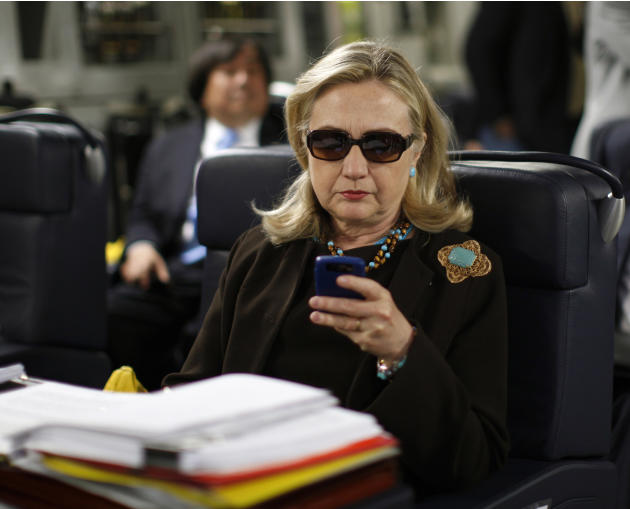 FILE - In this Oct. 18, 2011, file photo, then-Secretary of State Hillary Rodham Clinton checks her Blackberry from a desk inside a C-17 military plane upon her departure from Malta, in the Mediterran
