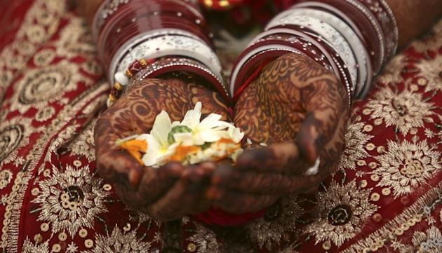 A bride holds flowers with her hands decorated with henna paste during her wedding ceremony in the western Indian city of Ahmedabad Image (representational image) Credit: REUTERS